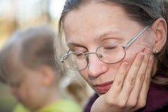 疲乏的母亲打盹的坐在她的女儿旁边 库存照片