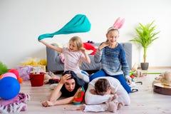 疲乏的父母和嬉戏的孩子 免版税库存图片