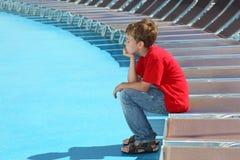 疲乏的男孩坐甲板椅子边缘  免版税图库摄影