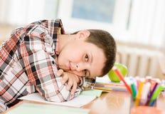疲乏的男小学生在教室 免版税图库摄影