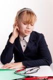 疲乏的白肤金发的女小学生画象有头疼的 免版税库存图片