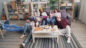 疲乏的睡觉在长沙发和地板的男人和妇女在舱内甲板的令人愉快的党以后 影视素材