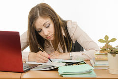 疲乏的老师检查学生笔记本 库存照片