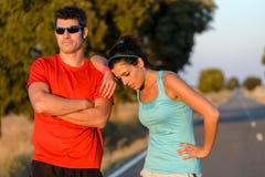 疲乏的运动员在跑在乡下公路以后 库存图片
