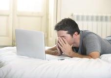 年轻疲乏的运转在计算机膝上型计算机无线的人说谎在床上的或长沙发在家连接了到技术概念的互联网 库存照片