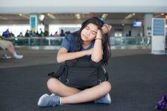 疲乏的青少年的女孩坐地板在有行李的机场 免版税库存照片