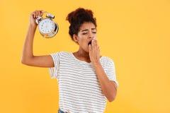 疲乏的非洲妇女哈欠和举行闹钟 库存图片