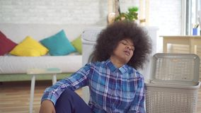 疲乏的非裔美国人的年轻女人主妇繁忙与家庭作业,用途洗衣机 股票视频