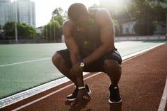 年轻疲乏的非洲男性运动员完成的跑 免版税库存照片