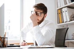 疲乏的年轻商人感人的眼睛 免版税库存图片