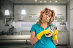 疲乏的主妇妇女洗涤的盘在厨房里 库存图片