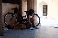 疲乏的asiat人睡眠和在地板上的自行车附近放松 免版税库存照片