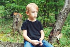 疲乏的liitle男孩坐休息的一本日志在森林里 免版税库存照片