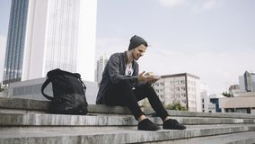 疲乏,但是愉快的游人坐在街道上的步并且拿着有午餐的板材 免版税库存图片