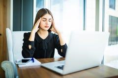 疲乏介意与考虑方式的顶头痛苦妇女完成在膝上型计算机的任务在桌上 库存照片