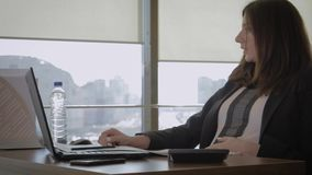 疲倦于在办公室饮用水的工作的孕妇商人从瓶 股票录像