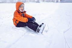 疲倦在训练男孩青少年在曲棍球冰鞋的雪近的滑冰的滑冰场 免版税库存照片