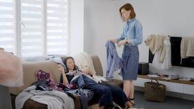 疲倦的客户女孩在衣裳堆的长沙发说谎,并且她的图象制造者站立近,采取褂子 股票视频