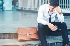 疲倦的或被注重的商人坐走道在工作以后 免版税库存图片