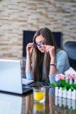 疲倦的沮丧的哀伤的妇女感觉担心坐在有膝上型计算机的办公室的问题,注重了沮丧的妇女麻烦与 免版税库存图片