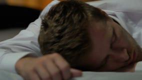 疲倦的男性自由职业者睡觉在床上的膝上型计算机附近的,疲乏的劳累过度的人,重音 股票视频