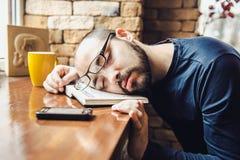 疲倦的玻璃的不剃须的人,睡着了在桌上 库存图片