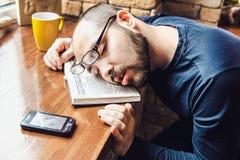 疲倦的玻璃的不剃须的人,睡着了在桌上 免版税库存图片