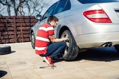 疲倦维护、损坏的汽车轮胎或者改变的季节性轮胎 更换一辆平车在后院疲倦 图库摄影