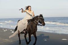 疾驰的马的妇女在海滩 库存照片