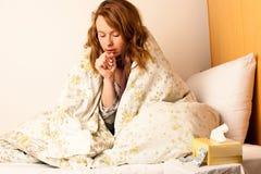 病态的妇女咳嗽在床上 免版税库存图片
