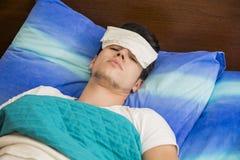 年轻病或不适的人在床上 免版税库存图片