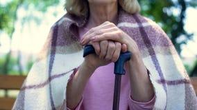 病残退休了妇女坐倾斜在拐棍,退休金生活方式的长凳 免版税库存照片