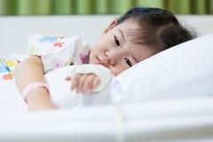 病症孩子在医院,盐静脉注射(iv)在手边亚洲人 库存照片
