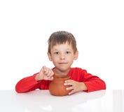 病的五岁的男孩坐在一张白色桌上并且吃与匙子 库存图片