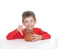 病的五岁的男孩坐在一张白色桌上并且吃与从泥罐的一把匙子 库存图片