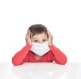 病的五岁的男孩坐在与医学医疗保健面具的一张白色桌上 免版税库存图片