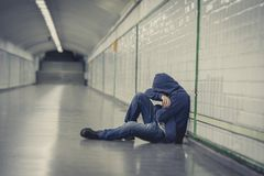 年轻病的人丢失了遭受的消沉坐地面街道地铁隧道 图库摄影