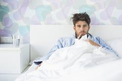 病的人画象有温度计的在家斜倚在床上的嘴 免版税图库摄影