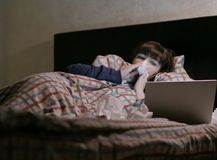病的俏丽的女孩在晚上在床上在并且观看膝上型计算机 免版税图库摄影