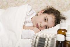 病的儿童女孩在床上 库存图片