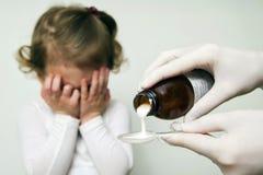 病的女婴等候她的倾吐在匙子的疗程 库存图片