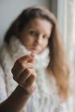 病的女孩在她的手上的拿着一种片剂 库存图片