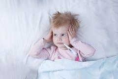 病的女孩,有温度计的孩子在一张嘴,在床上,疾病的概念 库存图片