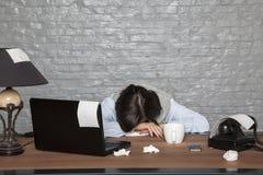 病的女实业家睡着了在有精疲力尽的书桌上 免版税图库摄影