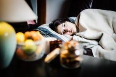 病的妇女在床,打电话请病假,休息日上从工作 检查温度的温度计热病 免版税库存图片