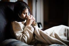 病的妇女在床,打电话请病假,休息日上从工作 饮用的清凉茶 维生素和热的茶流感的 图库摄影