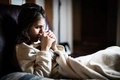 病的妇女在床,打电话请病假,休息日上从工作 饮用的清凉茶 维生素和热的茶流感的 免版税库存照片