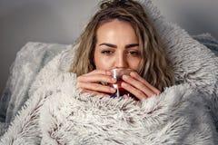 病的妇女在床,饮用的茶上 维生素和热的茶流感的 C 库存照片