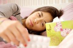 病的妇女在拿着药片的床上看它 库存图片