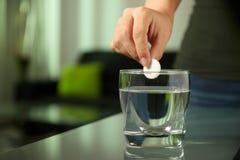 病的妇女在杯投入冒泡片剂阿斯匹灵水 免版税图库摄影